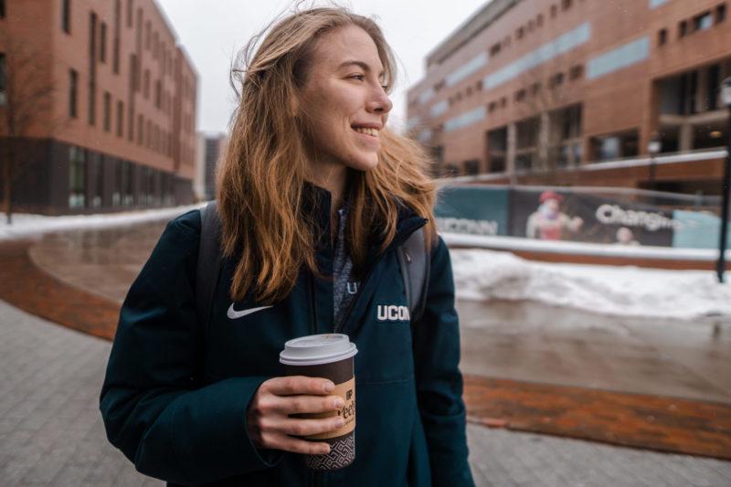 Tjej håller i en kaffe mugg, en vecka för en college fotbollsspelare