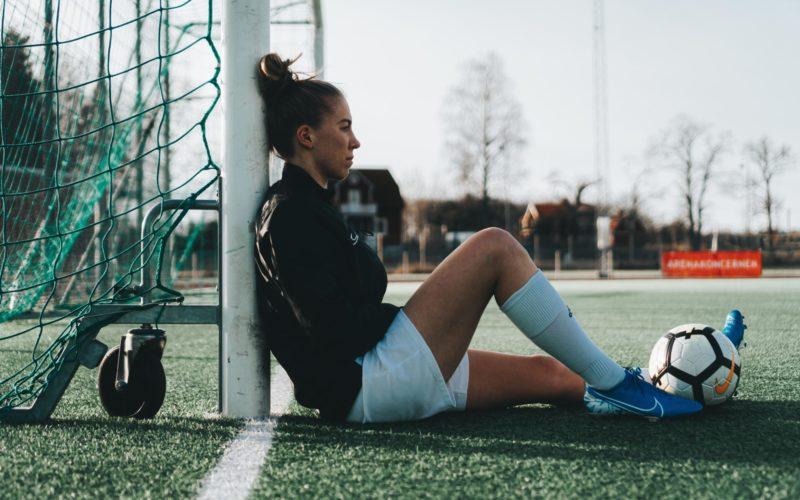 fotbollsspelare lutar sig mot stolpe